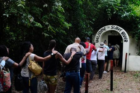 Members of a heritage tour group enact how slaves were transported at the Assin Manso river