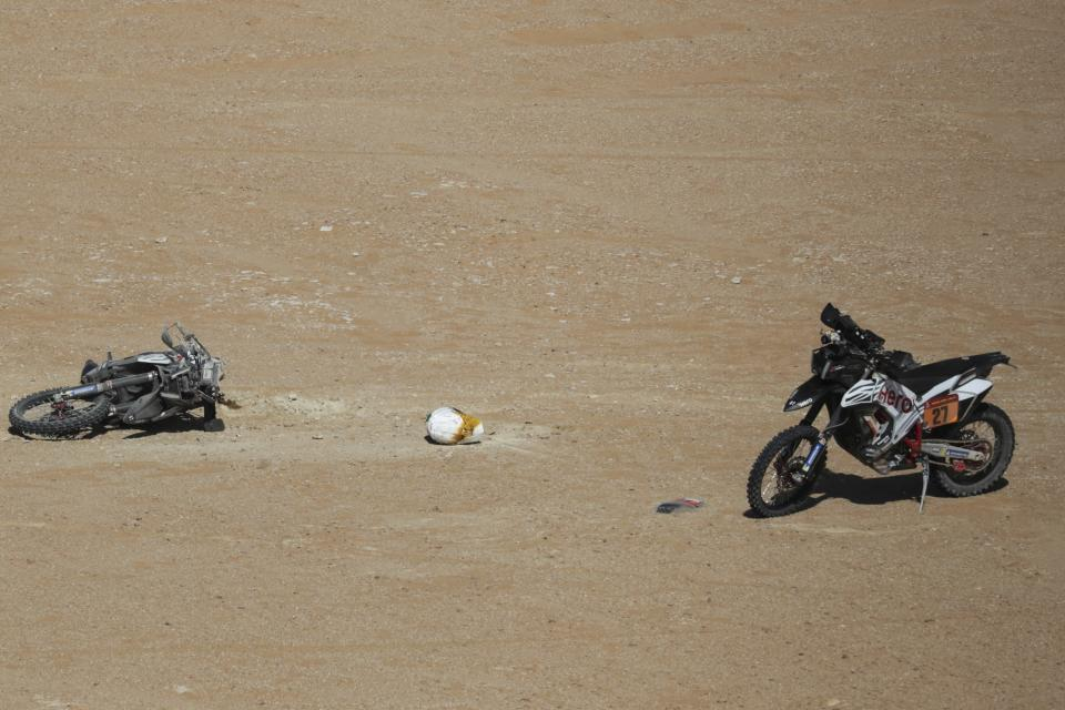 The Hero motorbike of Paulo Gonalves of Portugal lays on the ground, left, during stage seven of the Dakar Rally between Riyadh and Wadi Al Dawasir, Saudi Arabia, Sunday, Jan. 12, 2020. Gonalves, 40, died after an accident at kilometer 276. (AP Photo/Bernat Armangue)