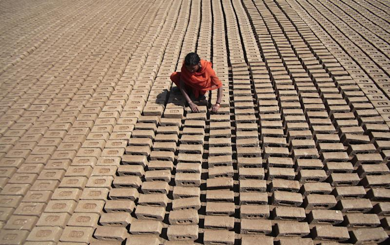10ThingsToSee - An Indian woman laborer works at a brick factory on International Women's Day on the outskirts of Jammu, India, Saturday, March 8, 2014. (AP Photo/Channi Anand)