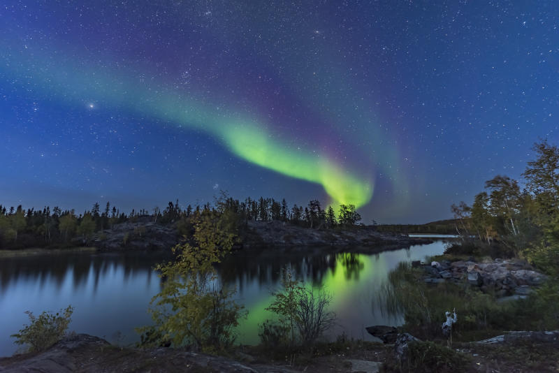 A display of Northern Lights starting up in the twilight, over the river leading out of Tibbitt Lake, at the end of the Ingraham Trail near Yellowknife NWT. (Photo by: VW Pics/Universal Images Group via Getty Images)
