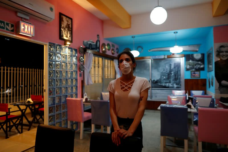 FILE PHOTO: A waitress watches the TV as she waits for costumers in a restaurant, following the outbreake of the coronavirus disease (COVID-19), in Buenos Aires