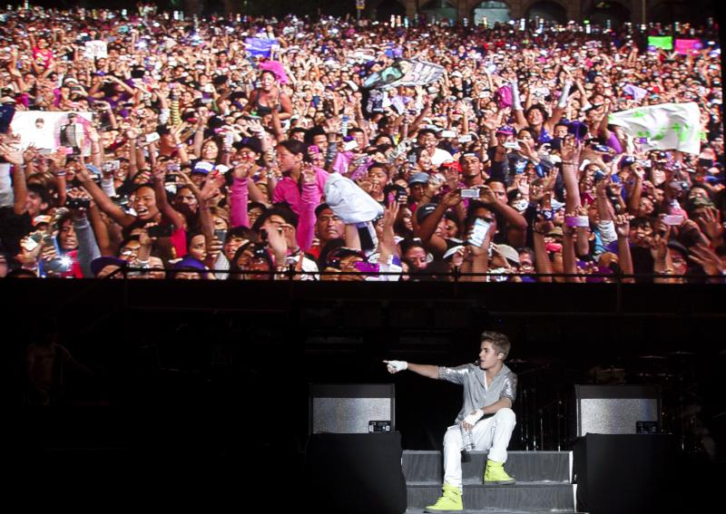 Sitting under a video screen that displays people attending his show, pop star Justin Bieber performs during a free open-air concert in Mexico City, Monday, June 11, 2012. (AP Photo/Alexandre Meneghini)