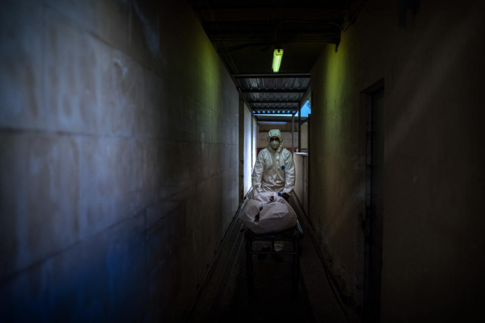 A mortuary worker transports the body of a COVID-19 victim on a stretcher at the morgue of a hospital in Barcelona, Spain, Thursday, Nov. 5, 2020. After successfully bringing the daily death count down from over 900 in March to single digits by July, Spain has seen a steady uptick that brought deaths back to over 200 a day this month. With that relapse, the body collectors have returned to making the rounds of hospitals, homes and care facilities. (AP Photo/Emilio Morenatti)