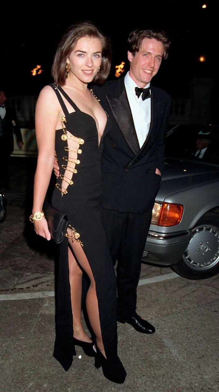"""<p>This safety pin-adorned Gianni Versace dress that Elizabeth wore to Hugh's premiere for <em>Four Weddings and a Funeral</em> is her most iconic look to date—and for good reason.</p><p>This history-making red carpet look was actually completely unplanned. Liz had nothing to wear for the event and Versace came through with one instantly iconic option at the last second, Hugh recently revealed in an <a href=""""https://uk.style.yahoo.com/hug..."""" data-ylk=""""slk:interview"""" class=""""link rapid-noclick-resp"""">interview</a>. </p>"""