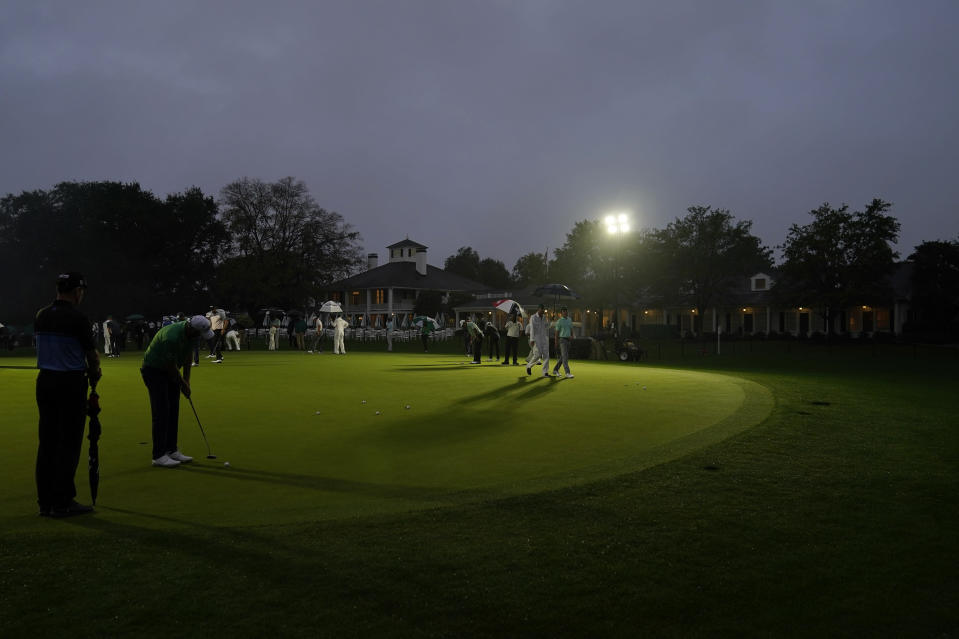 Golfers practice on the putting green next near the Augusta National Golf Course clubhouse before the start of the first round of the Masters golf tournament Thursday, Nov. 12, 2020, in Augusta, Ga. (AP Photo/David J. Phillip)