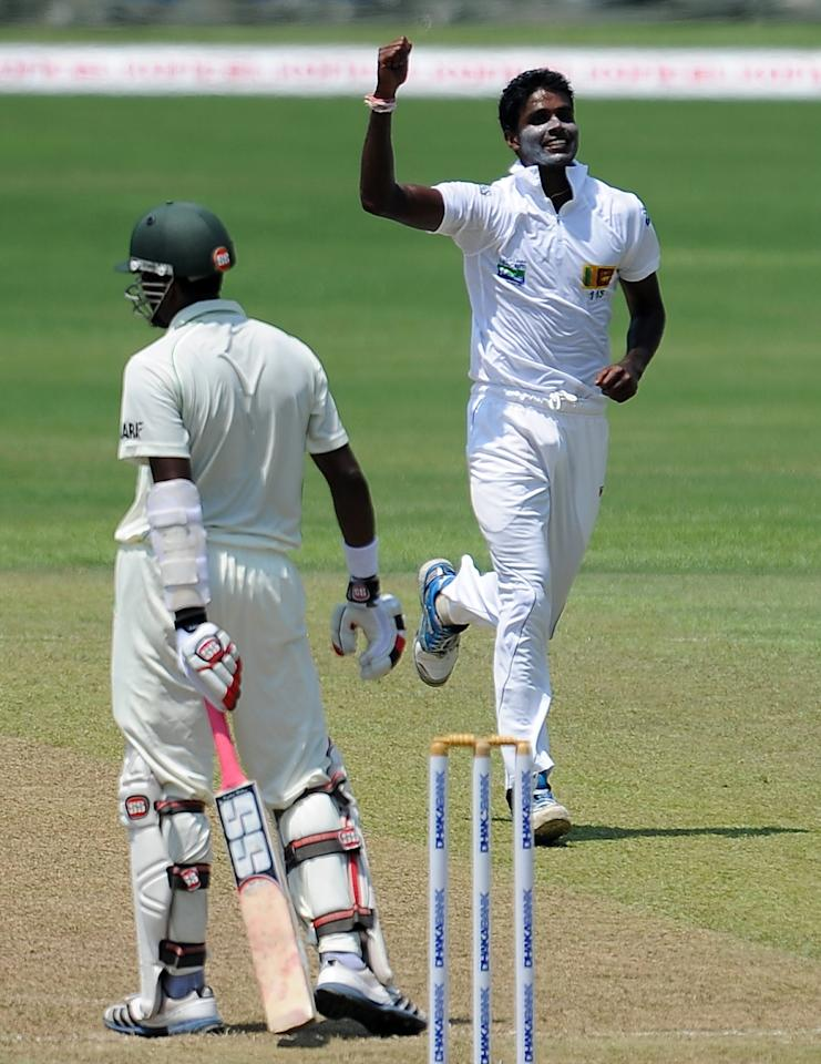 Sri Lanka's cricketer Shaminda Eranga (R) celebrates after he dismissed Bangladeshi cricketer Jahurul Islam (L) during the opening day of their second Test cricket match between Sri Lanka and Bangladesh at the R. Premadasa Cricket Stadium in Colombo on March 16, 2013.  AFP PHOTO/ LAKRUWAN