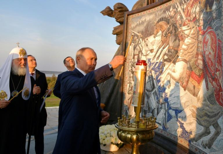 Russian President Vladimir Putin lights a candle unveiling a 50-tonne monument to legendary Russian medieval prince Alexander Nevsky (AFP/Alexey DRUZHININ)