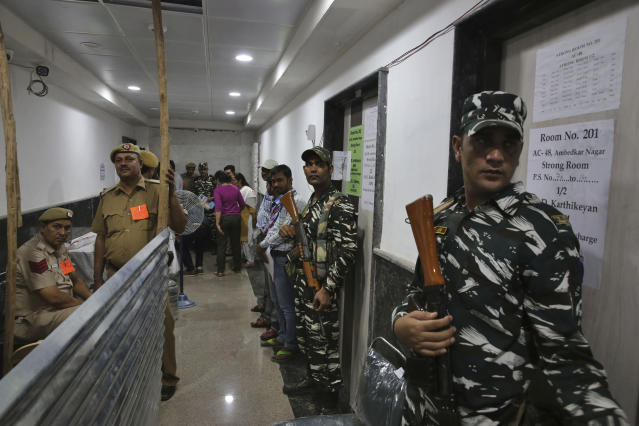 Indian paramilitary force soldiers stand guard outside a room where voting machines are stored as counting votes of India's massive general elections begins in New Delhi, India, Thursday, May 23, 2019. The count is expected to conclude by the evening, with strong trends visible by midday. (AP Photo/Manish Swarup)