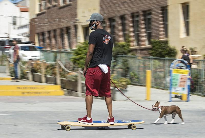 VENICE, CA-MAY 14, 2020: Ray Grey, 28, of Hollywood, wearing a mask to protect against the coronavirus,rmakes his way along the boardwalk in Venice Beach, on a long board with his dog Poet, a Boston Terrier running alongside. They are from Hollywood. A new rule, announced by Mayor Eric Garcetti on Wednesday, now requires face masks for all outdoor activities. (Mel Melcon/Los Angeles Times)