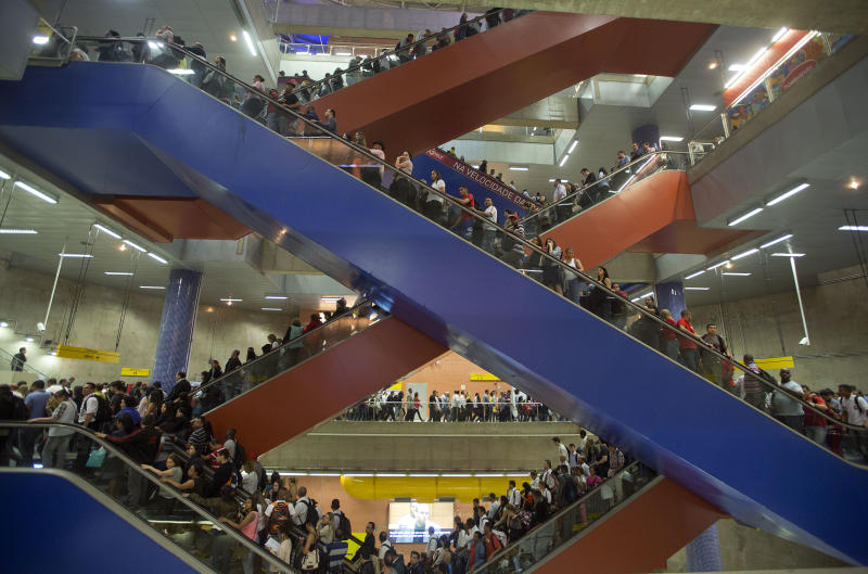 In this Aug. 7, 2013 photo, passengers ride escalators to access subway platforms in Sao Paulo, Brazil. Exhausted workers often travel two or three hours each way, crammed into tightly packed buses and subways. And that's if things work as planned. Commuter train breakdowns are common, and at times enraged commuters sometimes have clashed with police after being stranded. (AP Photo/Andre Penner)