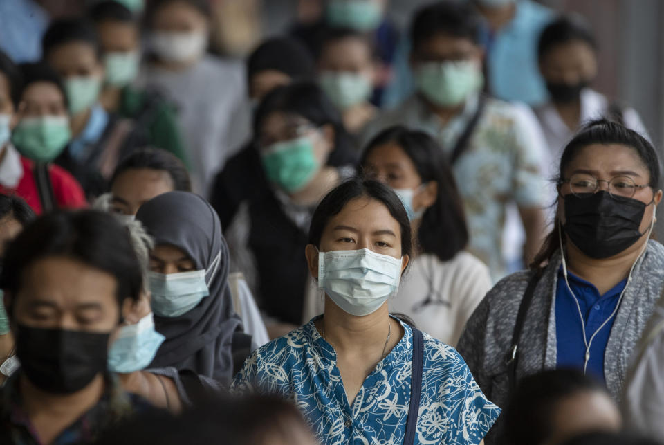 Office workers wearing face masks to help curb the spread of the coronavirus walk to work at Saen Saep pier in Bangkok, Thailand, Friday, April 16, 2021. (AP Photo/Sakchai Lalit)