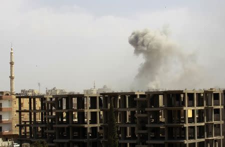 Smoke rises after what activists said was an air raid by Syrian government forces at the eastern Syrian city of Raqqa