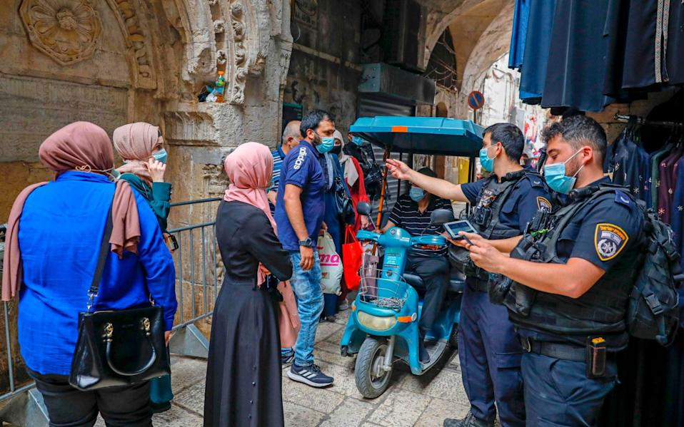 Israeli police officers enforce coronavirus regulations in Jerusalem's Old City - AFP