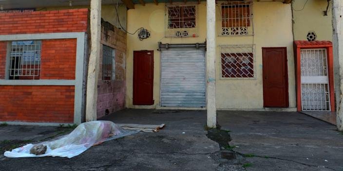 View of a body said to be laying for three days outside a closed clinic in Guayaquil, Ecuador on April 3, 2020. - Troops and police in Ecuador have collected at least 150 bodies from streets and homes in the country's most populous city Guayaquil amid warnings that as many as 3,500 people could die of the COVID-19 coronavirus in the city and surrounding province in the coming months.