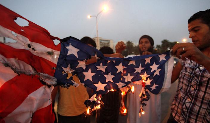 FILE - In this Sept. 14, 2012 file photo, Libyan followers of Ansar al-Shariah Brigades burn the U.S. flag during a protest in front of the Tibesti Hotel, in Benghazi, Libya. Small teams of U.S. special operations forces arrived at American embassies throughout North Africa to set up a new counterterrorist network months before militants killed the U.S. ambassador in Libya. But officials say the network was too new to stop the Benghazi attack. (AP Photo / Mohammad Hannon, File)