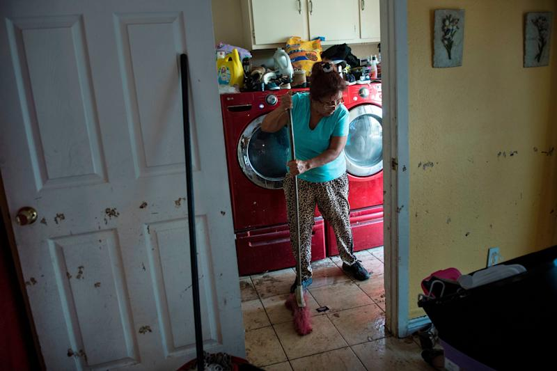 A woman cleans the floors of a once flooded house in Houston.