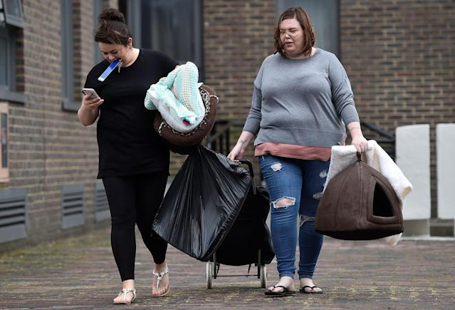 <p>People carry personal possessions as they leave the Dorney Tower residential block, as residents were evacuated as a precautionary measure following concerns over the type of cladding used on the outside of the buildings on the Chalcots Estate in north London, Britain, June 25, 2017. (Photo: Hannah McKay/Reuters) </p>
