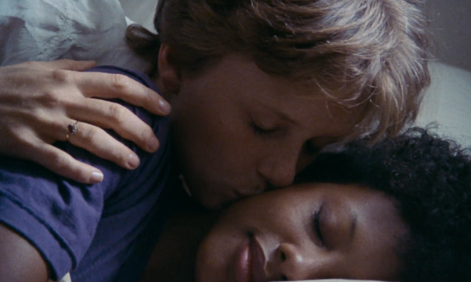 A lesbian couple, one white woman and one Black woman, embrace in bed