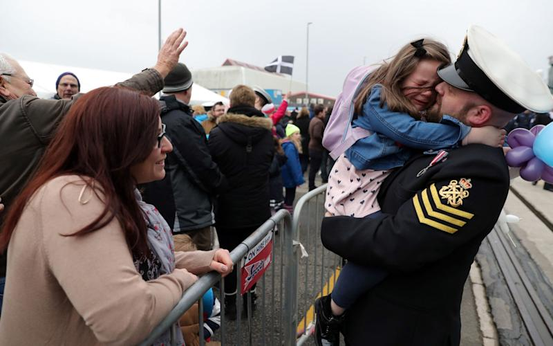 Petty Officer Adam Jeffrey (right) is greeted by his daughter Isabelle, 5, and wife Luisa (left) after coming ashore from HMS Ocean - Credit: Andrew Matthews/PA