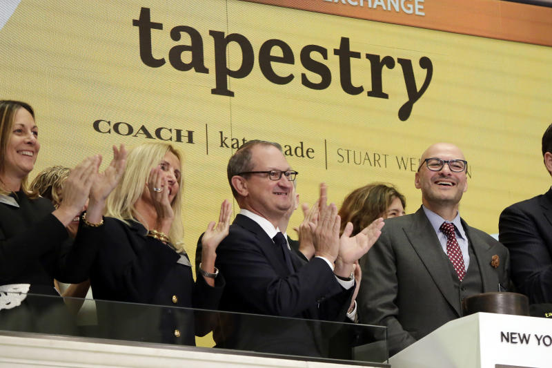 Tapestry Inc. CEO Victor Luis, right, home to Coach, Kate Spade and Stuart Weitzman brands, is applauded as he rings the New York Stock Exchange opening bell, Tuesday, Oct. 31, 2017. (AP Photo/Richard Drew)