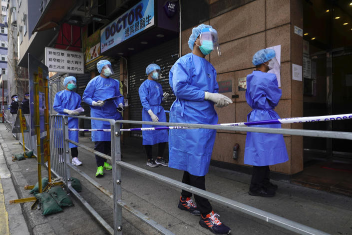 Government investigators wearing protective suits gather in the Yau Ma Tei area in Hong Kong, Saturday, Jan. 23, 2021. Thousands of Hong Kong residents will be locked down in an unprecedented move by the government to contain a worsening outbreak in the city, authorities said Saturday. (AP Photo/Vincent Yu)
