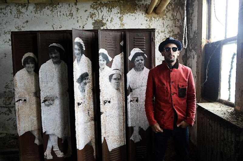 French artist JR with one of his artworks inside the Ellis Island Immigrant Hospital in New York on October 16, 2014 (AFP Photo/Jewel Samad)