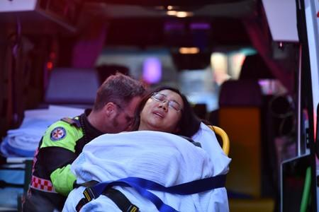 A woman is taken by ambulance, as police officers investigate a scene following reports of aa stabbing in Sydney