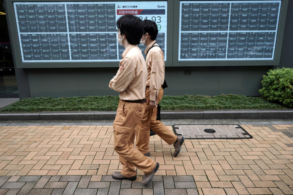 People walk past a blank electronic stock board supposedly showing Japan's Nikkei 225 index at a securities firm in Tokyo Thursday, Oct. 1, 2020. Trading on the Tokyo Stock Exchange was suspended Thursday because of a problem in the system for relaying market information. (AP Photo/Eugene Hoshiko)