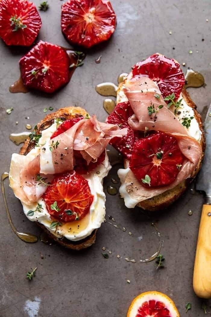 Two toasts topped with ricotta, prosciutto, and honey drizzle.