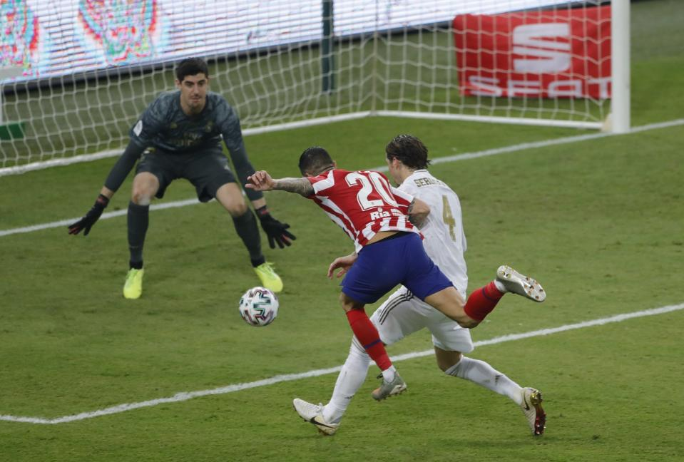 Atletico Madrid's Vitolo shoots the ball as Real Madrid's Sergio Ramos tries to stop him during the Spanish Super Cup Final soccer match between Real Madrid and Atletico Madrid at King Abdullah stadium in Jiddah, Saudi Arabia, Monday, Jan. 13, 2020. (AP Photo/Amr Nabil)