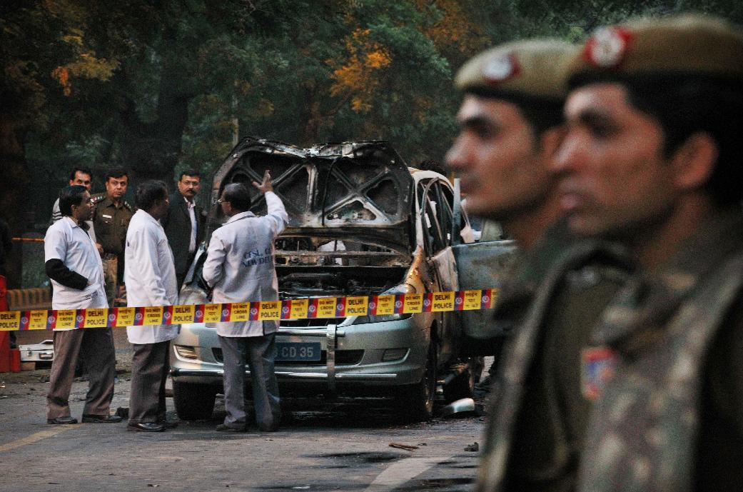 Indian police forensics experts investigate after an explosion tore through a car belonging to the Israel Embassy, center, in New Delhi, India, Monday, Feb. 13, 2012. The wife of an Israeli diplomat was injured in the explosion , the same day as an Israeli Embassy staffer in Georgia found a bomb underneath his car, which was dismantled before exploding, according to Indian and Israeli media reports.(AP Photo/Kevin Frayer)