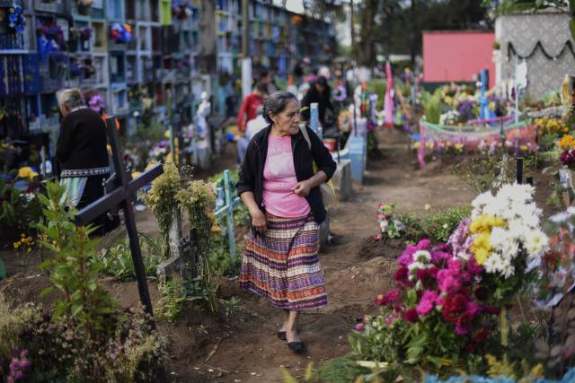 <p>A man adorns a grave at the municipal cemetery of Villa Nueva, 25 km south of Guatemala City, during the celebration of All Saints' Day on Nov. 1, 2017. (Photo: Johan Ordonez/AFP/Getty Images) </p>