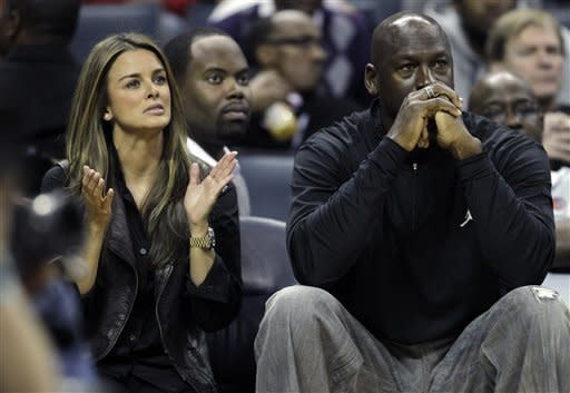 Charlotte Bobcats owner Michael Jordan, right, sits with his fiance Yvette Prieto, left, during the first half of an NBA basketball game between the Charlotte Bobcats and the Cleveland Cavaliers in Charlotte, N.C., Monday, Jan. 16, 2012. (AP Photo/Chuck Burton)
