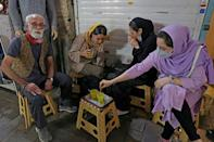 Given the miniature size of the teahouse, there are no tables, but customers can pull up a plastic stool outside, amid the bazaar's bustle (AFP/ATTA KENARE)