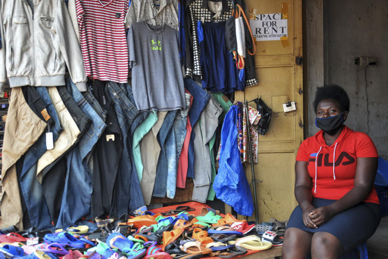 In this photo taken Saturday, June 20, 2020, Grace Twisimire, 25, sits in her once-thriving shop selling clothes and plastic shoes in the capital Kampala, Uganda. The COVID-19 pandemic means that millions of women in Africa and other developing regions could lose years of success in contributing to household incomes, asserting their independence and expanding financial inclusion. (AP Photo/Ronald Kabuubi)