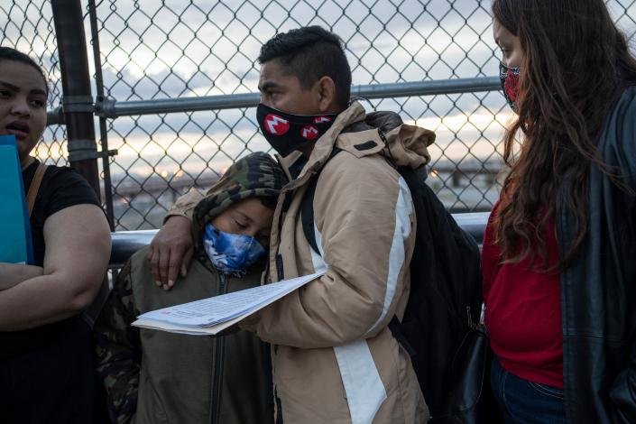 """Cesar, 35, an asylum seeker from Nicaragua waits with his wife, Carolina, 25, (Right) and his eight-year-old son Donovan to enter the US port of entry to change their asylum court dates on April 6, 2020 at the Paso del Norte International Bridge in Ciudad Jua?rez in the state of Chihuahua, Mexico. - As immigration courts have been closed due to the coronavirus, COVID-19, pandemic people seeking asylum in Migrant Protection Protocols program, better known as the """"Remain in Mexico"""" policy, are still expected to show up in the dangerous city centre before dawn to receive new dates despite stay-at-home order on both sides of the border. (Photo by Paul Ratje / Agence France-Presse / AFP) (Photo by PAUL RATJE/Agence France-Presse/AFP via Getty Images)"""