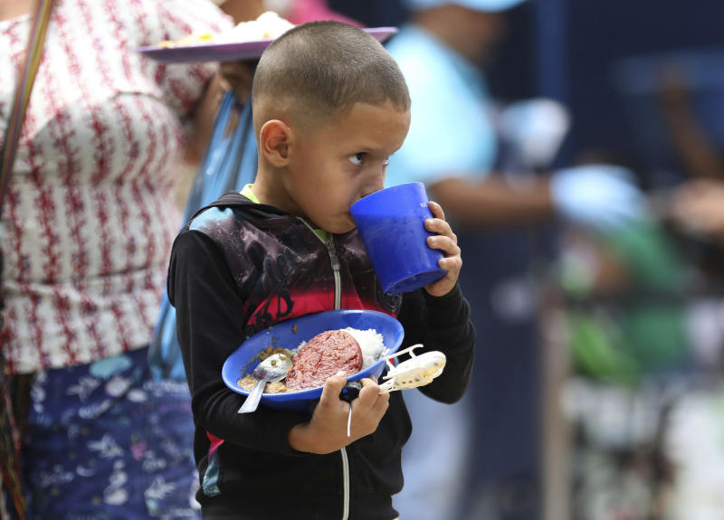 """A boy takes a sip of a grape-flavored drink as he holds onto his free lunch at the """"Divina Providencia"""" migrant shelter in La Parada, near Cucuta, Colombia, on the border with Venezuela, Monday, Feb. 18, 2019. The director of the shelter says they serve about 4,500 lunches per day, mostly to Venezuelan migrants, everyday of the week with the exception of Sunday. (AP Photo/Fernando Vergara)"""