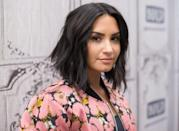 <p>Nothing complements a round face like a middle part with textured waves. Try Demi Lovato's dark brunette style for an easy summer style.</p>