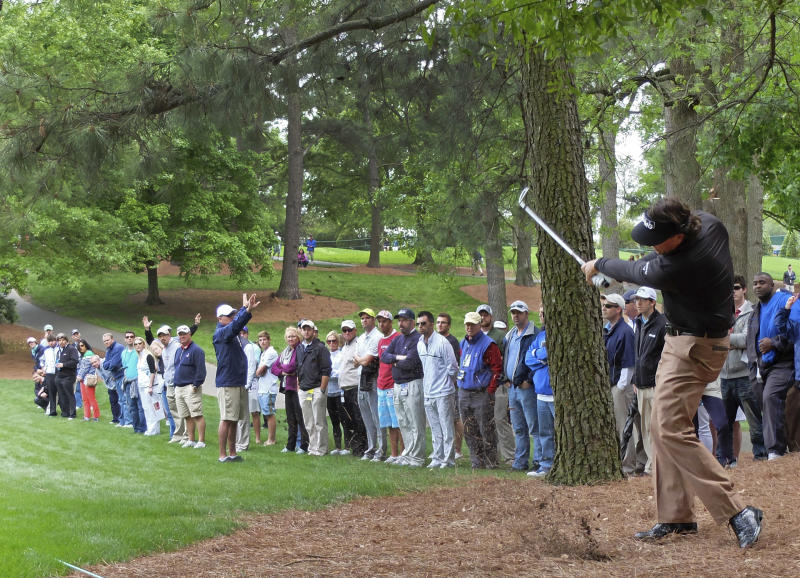 Phil Mickelson hits from the rough on the fifth hole during the third round of the Wells Fargo Championship golf tournament at Quail Hollow Club in Charlotte, N.C., Saturday, May 4, 2013. (AP Photo/Chuck Burton