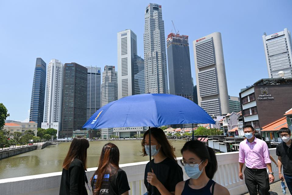 People walk along a bridge next to the financial business district in Singapore on April 20, 2021. (Photo by Roslan RAHMAN / AFP) (Photo by ROSLAN RAHMAN/AFP via Getty Images)