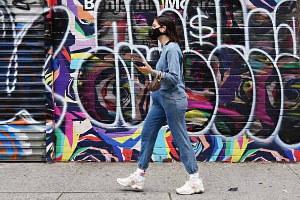 A woman wearing a protective mask walks by a colourful mural during the coronavirus pandemic in New York City.