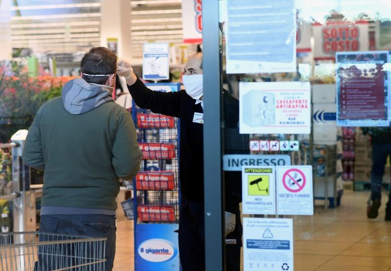 FILE PHOTO: An employee controls the temperature of a man at the entrance of a supermarket, as the spread of the coronavirus disease (COVID-19) continues, in Milan