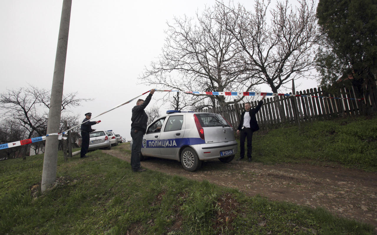 Police officers guard a house in village of Velika Ivanca, Serbia, Tuesday, April 9, 2013. A 60-year-old man gunned down 13 people, including a baby, in a house-to-house rampage in a quiet village on Tuesday before trying to kill himself and his wife, police and hospital officials said. (AP Photo/Darko Vojinovic)