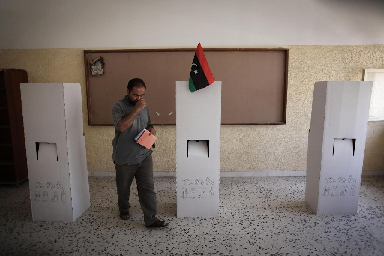 A Libyan man leaves a voting booth to cast his ballot at a polling station in the former loyalist stronghold district of Abu Salim in Tripoli, Libya, Saturday, July 7, 2012. Jubilant Libyans marked a major step toward democracy after decades of erratic one-man rule, voting Saturday in the first parliamentary election after last year's overthrow and killing of longtime dictator Moammar Gadhafi. But the joy over the historic vote was tempered by boycott calls, the burning of ballots and other violence in Libya's restive east.(AP Photo/Manu Brabo)