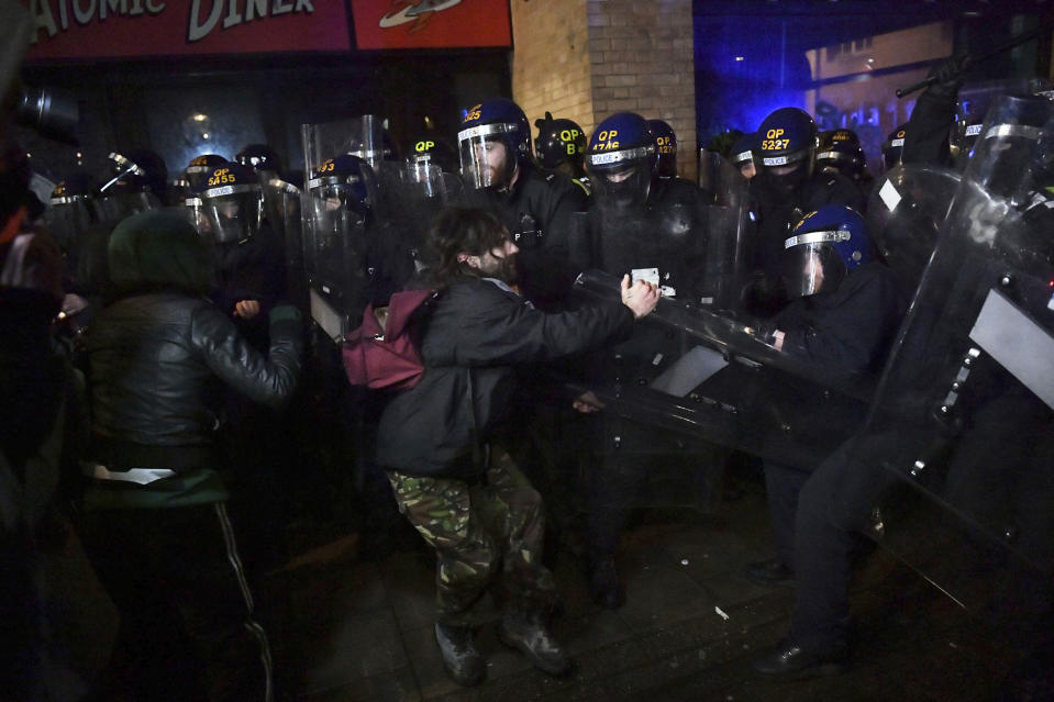 """Police officers move in on demonstrators during the """"Kill The Bill"""" protest in Bristol, England, Friday, March 26, 2021. Protesters are calling to protect free speech and protesting against new powers to be given to the police to impose conditions on non-violent protests, including those deemed too noisy or a nuisance. (Ben Birchall/PA via AP)"""
