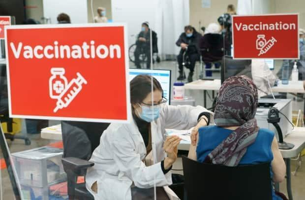 The Olympic Stadium may not get much use these days in Montreal, but it was certainly busy on Monday as hundreds of seniors showed up to get a dose of a vaccine that could save their lives. (Paul Chiasson/The Canadian Press - image credit)