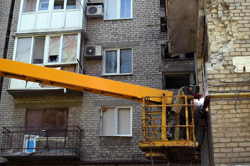 A man repairs the damage to a building caused by shelling in Donetsk, on September 5, 2014 (AFP Photo/Francisco Leong)