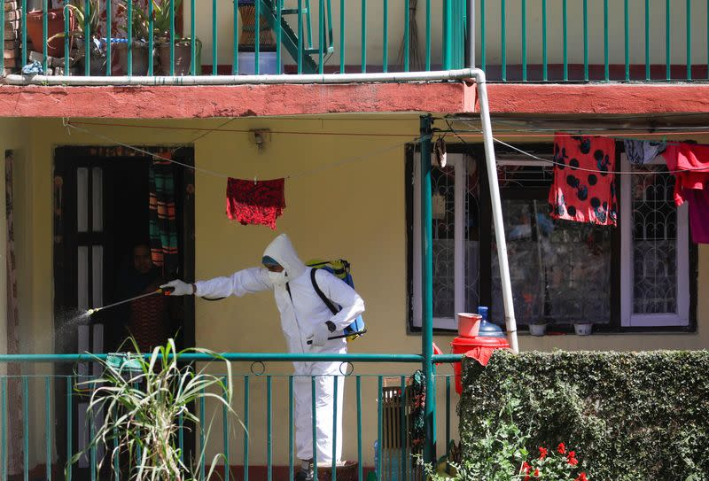 A volunteer sprays disinfectant outside a house during the tenth day of the lockdown imposed by the government amid concerns about the spread of coronavirus disease (COVID-19) outbreak, in Kathmandu