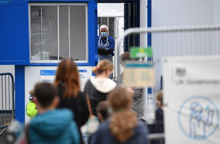 Members of the public queue to enter a temporary Covid-19 testing centre set up a car park in Kendal in Cumbria, north west England on June 21, 2021, following an outbreak of a coronavirus variant of concern. (Photo by Oli SCARFF / AFP) (Photo by OLI SCARFF/AFP via Getty Images)