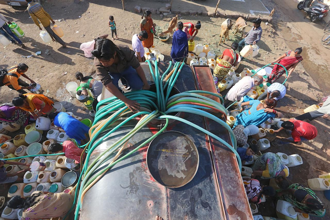 <p>Indian slum dwellers collect potable water from a municipal water tanker in Durga Nagar area of Bhopal on March 21, 2018. Slum dwellers depend on government supplies for drinking water and struggle to get adequate supply during summers. World Water Day is observed on March 22 and focuses on the importance of universal access to clean water, sanitation and hygiene facilities.<br /> AFP </p>
